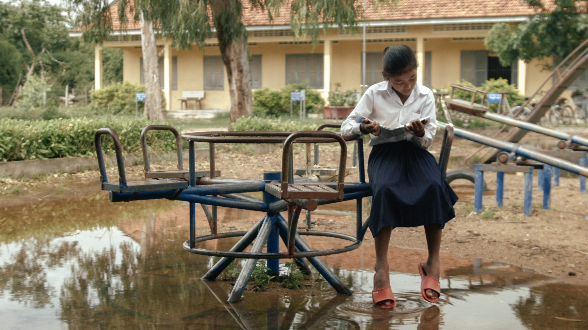 Cambodian girl enjoying access to more books thanks to an Australian Aid + ChildFund literacy project