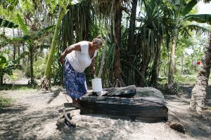 Elizabeth Ila draws water from her well in Gereka settlement, Port Morseby, Papua New Guinea. In the recent drought, the well ran dry for two months.