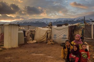 """Family by the fire in the ditch, West Bekaa  Hamad and his family, including ten children ages 2 to 17, live in tents made of tarps on the fringes of agricultural land in West Bekaa, Lebanon. Nearby are large peach and apple orchards and fields where sheep graze. Hamad says there are 300 refugees living in this area.  """"We came here from Syria four years ago,"""" Hamad says.  """"We rent this place to live and we work in the fields for money. But this time of year there is no farm work,"""" he says. """"Without regular work, I've fallen into debt for rent and food.""""  A cold February wind blows from the snow-covered mountains nearby. As the late afternoon light fades and the temperature drops, the family and neighbors gather in a roadside ditch in front of their shelters to warm themselves by a bonfire. Black, oily and foul-smelling smoke billows from the flames. The fire is fueled with trash they've gathered, most of it plastic.  The family received a water tank and latrine from World Vision, but there is no water delivery in the area."""